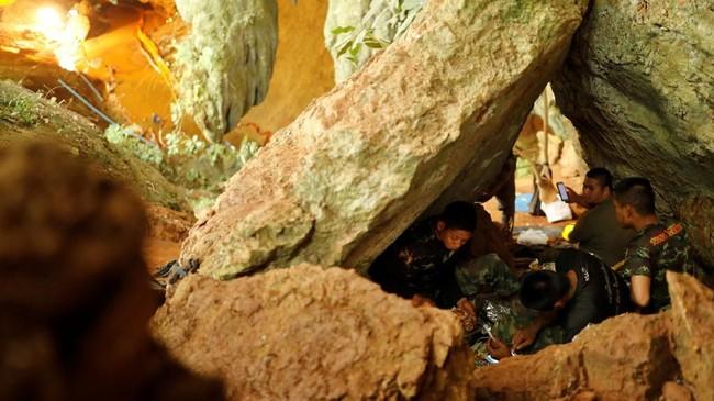 Tim penyelamat beristirahat di dalam gua Tham Luang, Thailand di mana 12 remaja dan pelatih sepak bolanya terjebak selama berhari-hari. (REUTERS/Tyrone Siu)
