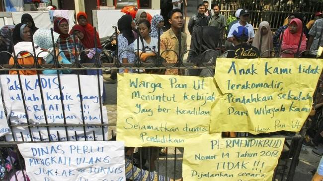 Puluhan orang tua muridmenggelarunjuk rasa dengan menyegel gerbang sekolah SMP 23 Tangerang di Panunggangan Utara, Tangerang, Banten, Senin (9/7). Anak mereka tidak diterima di sekolah tersebutyang menggunakan sistem zonasi. (ANTARA FOTO/Muhammad Iqbal)