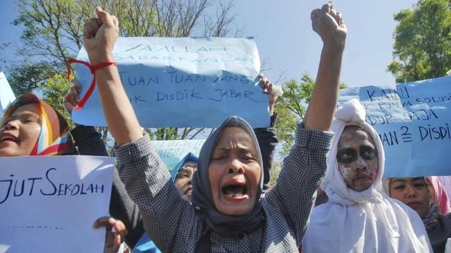 Sejumlah warga melakukan aksi unjuk rasa sistem Zonasi Sekolah di depan Gedung Sate, Bandung, Jawa Barat, Senin (9/7). Mereka menentang sistem zonasi dan sistem penerimaan siswa miskin yang dianggap tak tepat sasaran pada penerimaan peserta didik baru di SD, SMP, dan SMA. (ANTARA FOTO/Heru Salim)