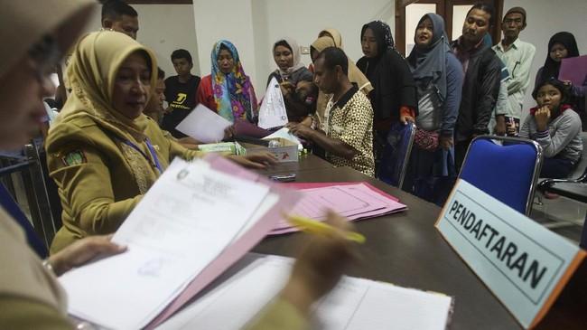 Siswa didampingi wali siswa mengantre untuk mendaftar SMP di kantor Dinas Pendidikan Kota Solo, Jawa Tengah, Senin (25/6). Sistem zonasi diterapkan untuk pemerataan akses dan mutu pendidikan serta mendekatkan satuan pendidikan dengan tempat tinggal peserta didik. (ANTARA FOTO/Maulana Surya)