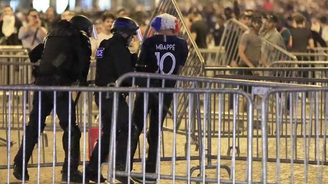 Polisi Prancis terpaksa turun tangan dan mengamankan sejumlah suporter sepak bola yang terlalu gembira atas kemenangan Timnas Prancis yang lolos babak final Piala Dunia 2018. (REUTERS/Gonzalo Fuentes)