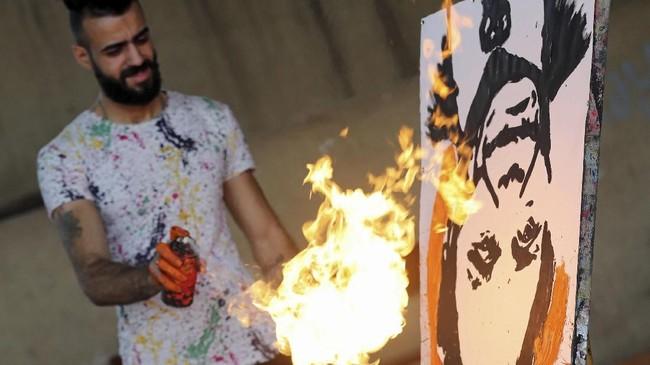 Magdy mampu membuat sebuah lukisan potret berbagai tokoh dengan amat cepat, beberapa menit, dari bawah ke atas. (REUTERS/Mohamed Abd El Ghany)