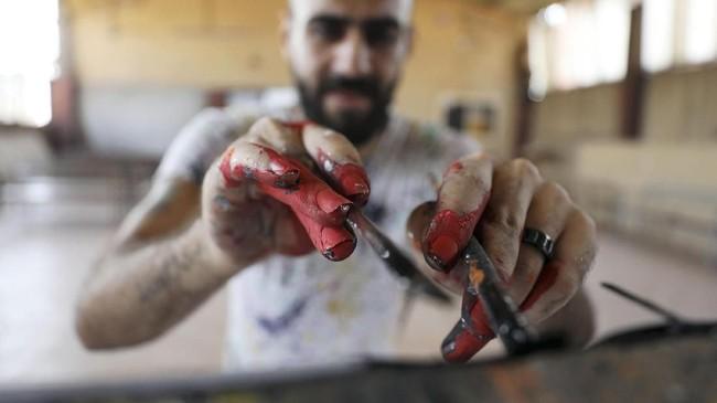 Seorang seniman asal Mesir mampu membuat lukisan dengan cepat, hanya beberapa menit. (REUTERS/Mohamed Abd El Ghany)