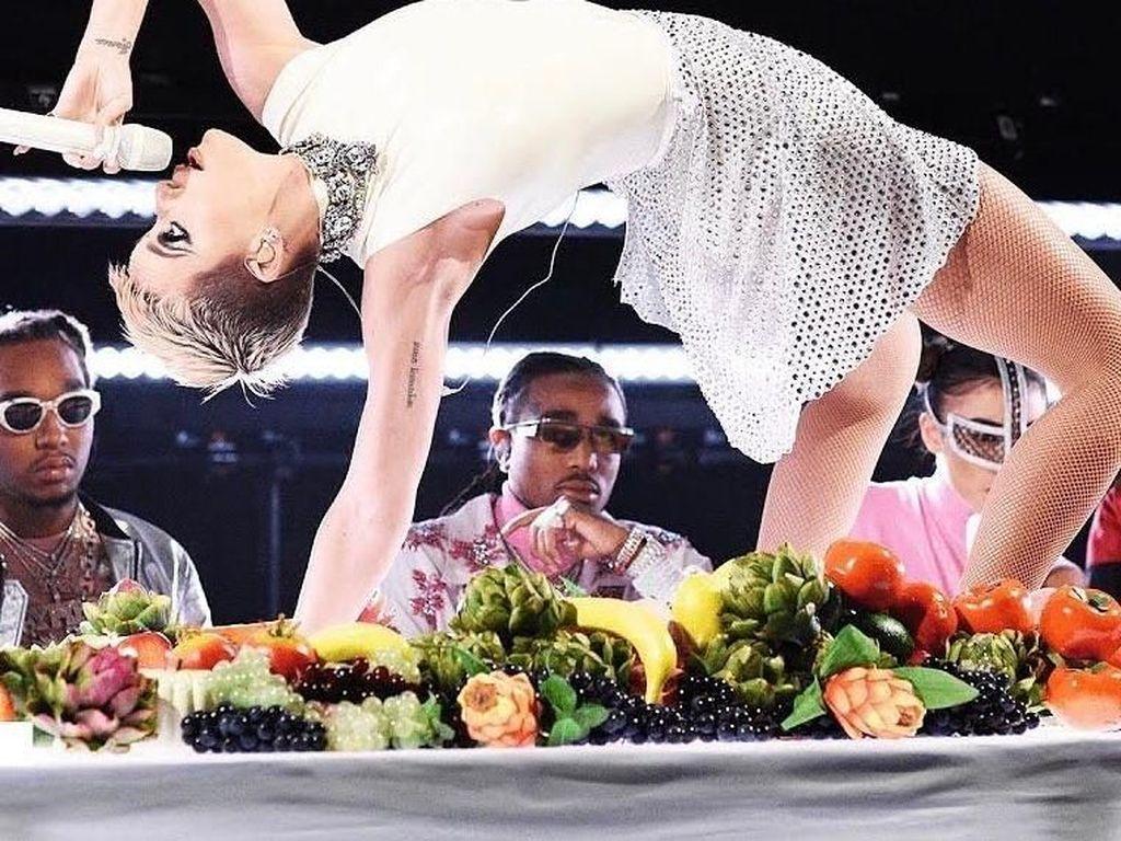 Punya aksi konser yang unik. Katy bernyanyi sambil memperagakan posisi yoga, di atas meja makan penuh dengan buah dan sayuran. Keren! Foto: Instagram @katyperry