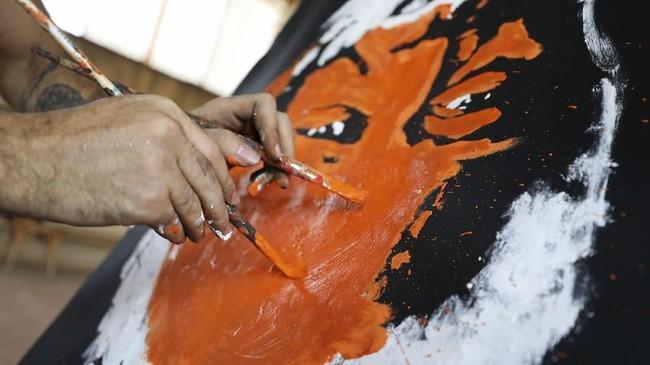 Magdy menggunakan bedak untuk menonjolkan rupa gambar, dan api untuk menciptakan corak warna pada kanvasnya. (REUTERS/Mohamed Abd El Ghany)