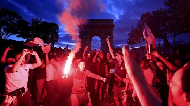 Warga Prancis merayakan kemenangan tim nasional mereka atas kesebelasan Belgia dalam pertandingan semi-final Piala Dunia 2018 di Champs Elysees, Paris. (REUTERS/Gonzalo Fuentes)