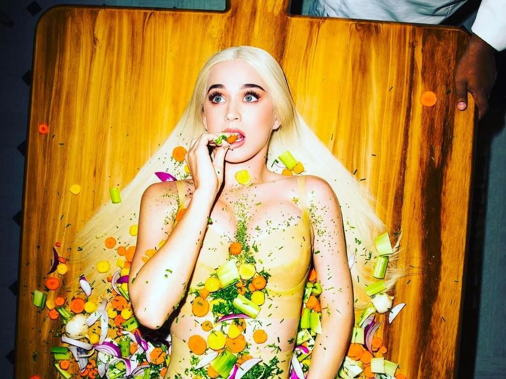 Dalam salah satu video musiknya, Katy tampil cantik, elegan, dan unik. Bermandikan potongan dan irisan sayuran, di atas papan kayu. Foto: Instagram @katyperry