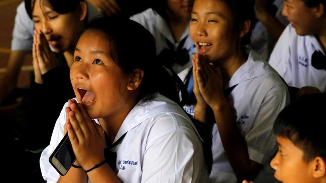 Doa suka cita didaraskan siswa Sekolah Mae Sai Prasitsart, Chiang Rai, Thailand setelah guru mereka mengumumkan bahwa teman sekelas mereka yang terjebak di gua telah berhasil diselamatkan, Senin (9/7). (REUTERS/Tyrone Siu TPX IMAGES OF THE DAY)