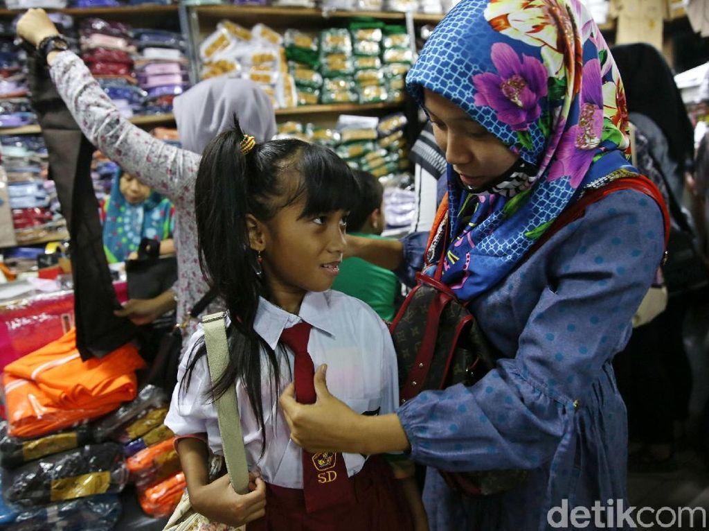 Seorang anak tersipu malusaat menjajal seragam Sekolah Dasar.