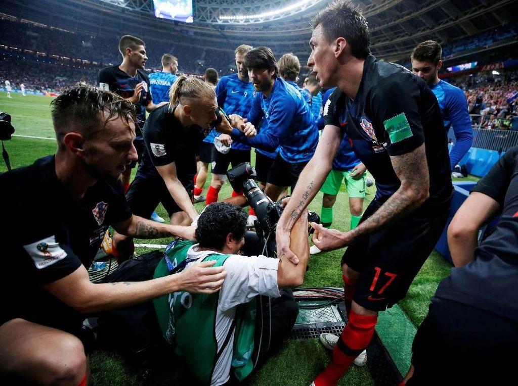 Usai tertindih, si fotografer dibantu untuk bangun oleh para pemain Kroasia. Foto: Reuters