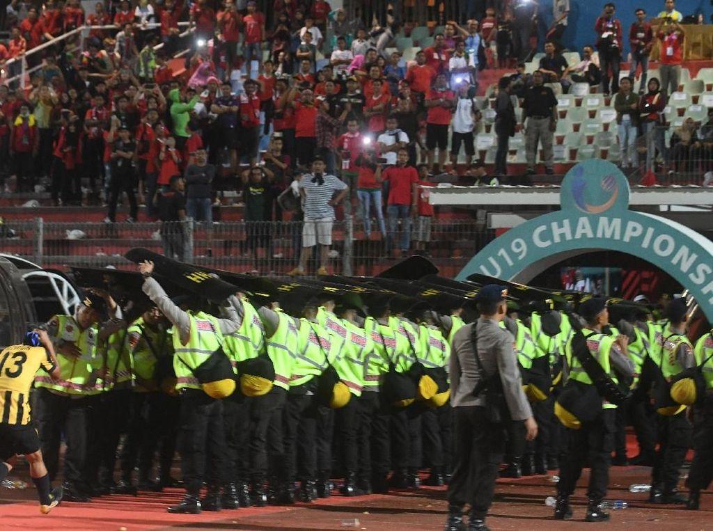 Saat akan keluar lapangan, para pemain Malaysia harus mendapat pengawalan polisi. ANTARA FOTO/Zabur Karuru.