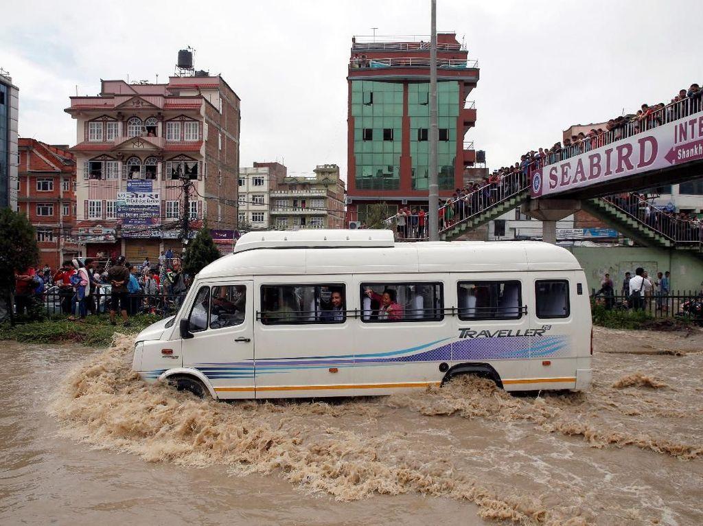Ratusan keluarga harus mengungsi untuk sementara waktu karena area pemukiman mereka digenangi air. Navesh Chitrakar/Reuters.