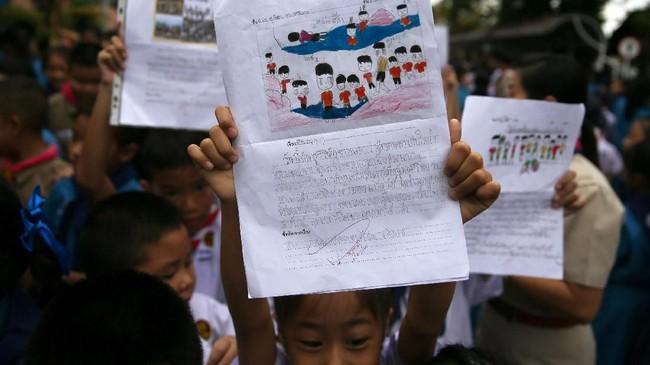Para siswa menunjukkan karya mereka di depan Rumah Sakit Chiang Rai Prachanukroh, tempat 12 remaja dan pelatihnya dirawat selepas dari gua. (REUTERS/Athit Perawongmetha)