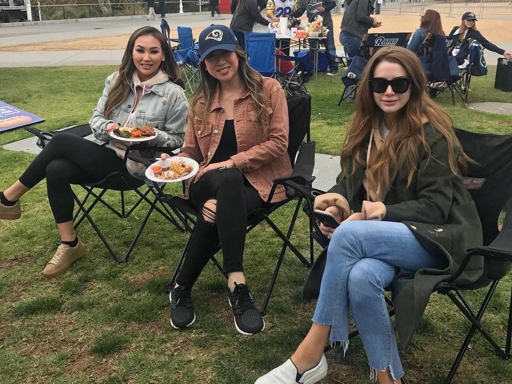 Wanita cantik berusia 28 tahun ini, memang tinggal di Amerika. Ini gaya santainya menikmati makan siang di pinggir lapangan brsama teman-temannya. Foto: Instagram @keziatoemion