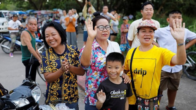 Warga di pinggir jalan melambaikan tangan ke arah ambulans yang membawa para remaja anggota tim sepak bola Wild Boars dan pelatihnya yang berhasil diselamatkan setelah terjebak selama tiga pekan di Gua Tham Luang, Chiang Rai, Thailand. (REUTERS/Tyrone Siu)