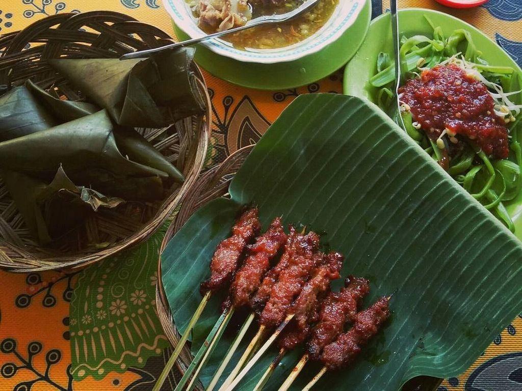Paket lengkap makan siang. Ada lontong, sate rembiga, bebalung (sop tulang) plecing kangkung dan sambal. Semuanya enak! Foto: Instagram @ajiher