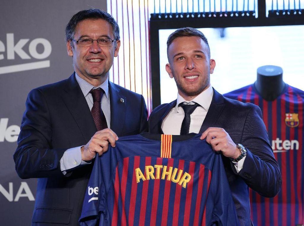 Didampingi Presiden Barca, Arthur tampak semringah memamerkan jersey klub barunya yang berwarna merah biru. (Foto: Albert Gea/Reuters)