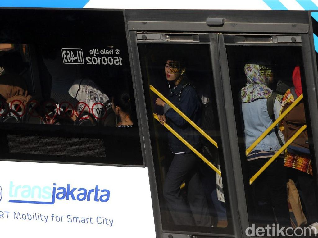 Warga menaiki bus Transjakarta di Halte Harmoni, Jakarta, Jumat (13/7/2017).