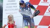 Valentino Rossi menyemprotkan sampanye di atas podium MotoGP Jerman. Rossi total sudah meraih lima finis podium di MotoGP 2018. (REUTERS/Fabrizio Bensch)