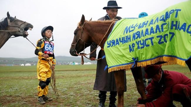 Seorang anak dan orangtuanya menyiapkan kuda untuk dipacu dalam Festival Naadam, di Ulaanbaatar, Mongolia. (REUTERS/B. Rentsendorj)