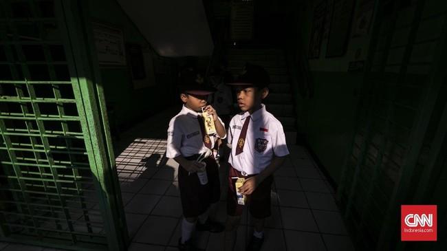Seluruh siswa baru mendapat jatah susu dan kacang hijau usai mengikuti upacara pada pertama sekolah di SDN Kampung Melayu 01/02, Jatinegara, Jakarta Timur. (CNNIndonesia/Adhi Wicaksono).