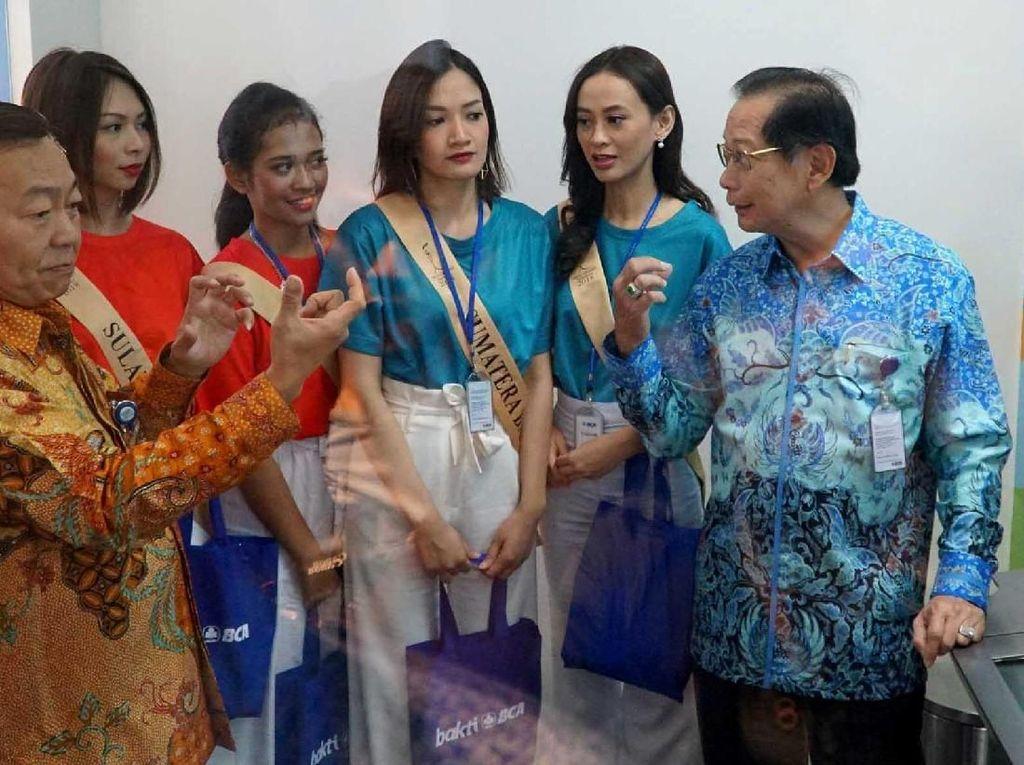 Presiden Direktur PT Bank Central Asia Tbk (BCA) Jahja Setiaatmadja (kanan) didampingi oleh Direktur BCA Santoso (kiri) bersama para finalis Miss Grand Indonesia 2018 melakukan experience di Video Banking BCA di sela kunjungan Finalis Miss Grand Indonesia ke BCA Learning Institute (BLI) di Bogor, Senin (16/07). Pool/BCA.