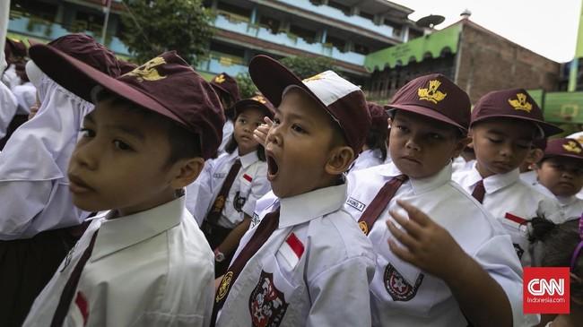 Para siswa-siswi berbaris mengikuti upacara pada pertama sekolah di SDN Kampung Melayu 01/02, Jatinegara, Jakarta Timur. (CNNIndonesia/Adhi Wicaksono)0.