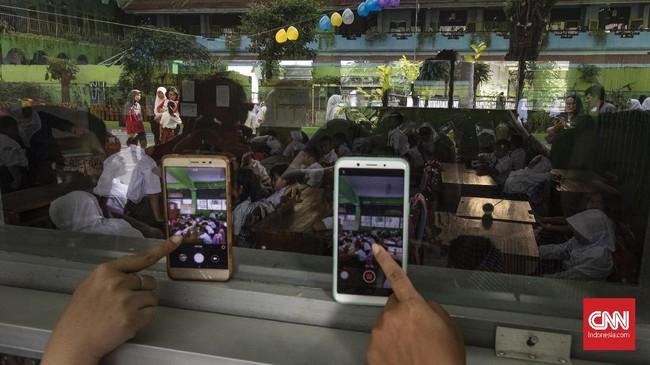 Sejumlah orang tua menggunakan ponsel untuk merekam kegiatan anak-anak mereka di hari pertama sekolah di SDN Kampung Melayu 01/02, Jatinegara, Jakarta Timur. (CNNIndonesia/Adhi Wicaksono).
