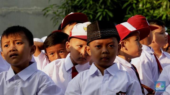 Suasana pelajar mengikuti upacara hari pertama masuk sekolah di SD Negeri 15 & 16 Klender, Jakarta Timur, Senin (16/7). Memasuki hari pertama sekolah, siswa dan siswi diberi pengenalan sekitar lingkungan sekolah. Mengacu pada peraturan pemerintah Sekolah diwajibkan melaksanakan Masa Pengenalan Lingkungan Sekolah (MPLS) sebagai pengganti Masa Orientasi Sekolah (MOS). Tujuan utama MPLS adalah membangun suasana ramah, aman, nyaman dan menyenangkan bagi calon siswa baru. Selain itu Menteri Pendidikan dan Kebudayaan atau Mendikbud, Muhadjir Effendy menyarankan wali murid atau orangtua siswa untuk mengantar putra-putrinya ke sekolah di hari pertama masuk sekolah. (CNBC Indonesia/Muhammad Sabki)