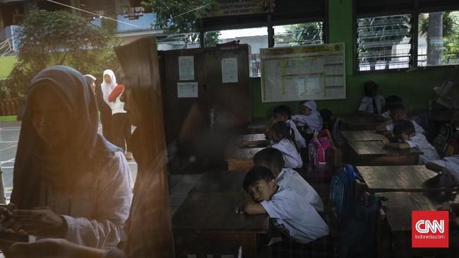 Sejumlah orang tua menunggu putra-putri mereka di hari pertama sekolah di SDN Kampung Melayu 01/02, Jatinegara, Jakarta Timur. (CNNIndonesia/Adhi Wicaksono).