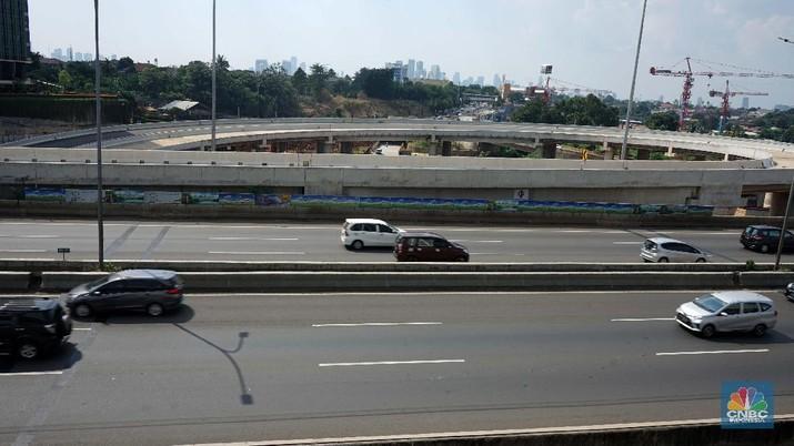 Kendaraan melintas di samping area pembangunan Tol Depok-Antasari (Desari), Jakarta, Rabu (20/6/2018).   Ruas Desari seksi 1A dengan panjang 5,8 kilometer tersebut rencana akan mulai beroperasi Juli mendatang, dan ditargetkan dalam satu hari dilalui 30.000 mobil. (CNBC Indonesia/Muhammad Sabki)