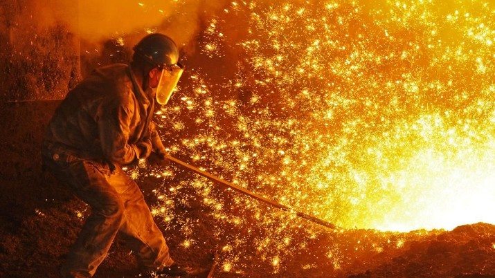 An employee works next to molten iron at a steel mill of Dongbei Special Steel in Dalian, Liaoning province, China July 17, 2018. REUTERS/Stringer  ATTENTION EDITORS - THIS IMAGE WAS PROVIDED BY A THIRD PARTY. CHINA OUT.