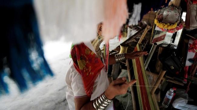 Di Chiang Rai, mereka mulai mengenal turisme. Beberapa anggota suku bahkan punya toko suvenir dan membuat barang dagangannya sendiri, dijajakan untuk wisatawan yang mampir. (REUTERS/Soe Zeya Tun)