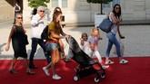 Istri Olivier Giroud (kanan), Jennifer Giroud beserta dua anaknya, Jade dan Evan, serta sang mertua ikut menyaksikan sang ayah diterima Presiden Prancis, Emmanuel Macron, di Elysee Palace. (REUTERS/Philippe Wojazer)