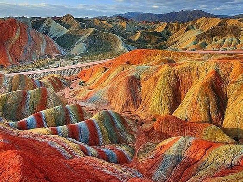 Pegunungan Pelangi di Zhangye Danxia, China memarken keindahan yang unik sekaligus menakjubkan. Pegunungan ini mengalami proses pelapukan dan erosi yang paling indah yang pernah ada. Warna-warna dramatis di seluruh gunung adalah hasil dari jejak mineral yang terkait dalam batu pasir dan mewarnai pasir dengan berbagai aneka warna. Istimewa/Pinterest.