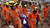Para pekerja menggunakan pemotong baja dan bor, dibantu anjing pelacak menyisir berton-ton beton dan logam. (REUTERS/Adnan Abidi)