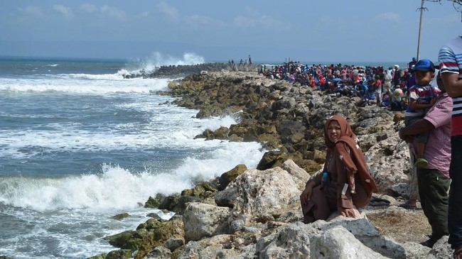 Warga memadati perairan untuk melihat proses evakuasi perahu nelayan karam diterjang ombak di Plawangan Puger, Jember, Jawa Timur, Kamis (19/7).(ANTARA FOTO/Seno)