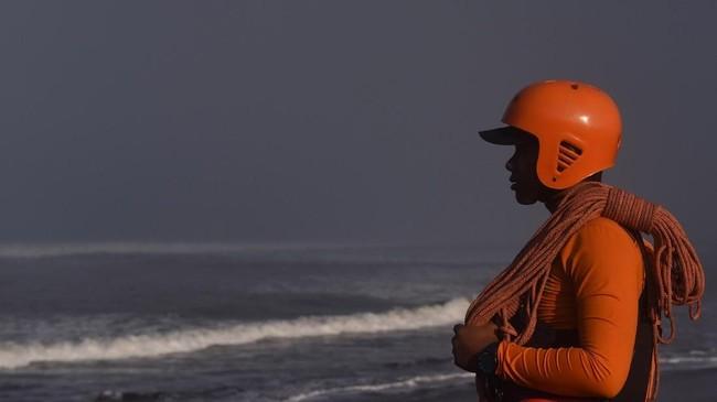 Anggota Basarnas menatap laut lepas sebelum melakukan pencarian korban di sekitar lokasi tenggelamnya perahu nelayan di perairan Plawangan Puger, Jember, Jawa Timur, Jumat (20/7).(ANTARA FOTO/Zabur Karuru)