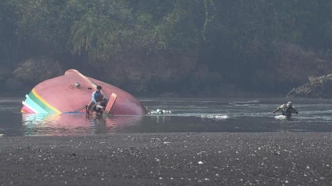 Warga membantu evakuasi bagian kapal nelayan yang tenggelam di perairan Plawangan Puger, Jember, Jawa Timur, Jumat (20/7). (ANTARA FOTO/Zabur Karuru)