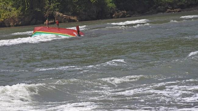 Warga berada di atas perahu nelayan yang tenggelam di perairan Plawangan Puger, Jember, Jawa Timur, Kamis (19/7). (ANTARA FOTO/Seno)