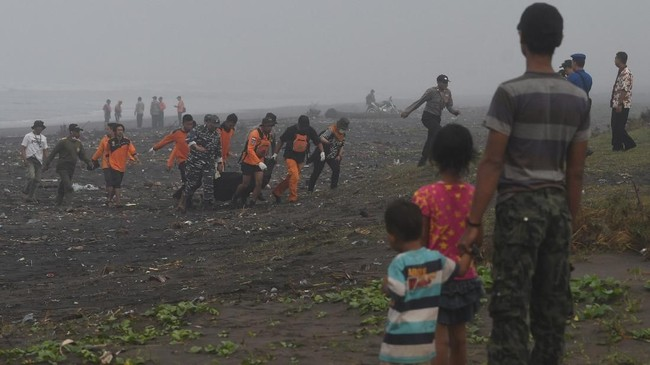Anggota Basarnas beserta warga mengangkut jenazah korban kapal tenggelam yang ditemukan di bibir pantai di perairan Plawangan Puger, Jember, Jawa Timur, Jumat (20/7). (ANTARA FOTO/Zabur Karuru)