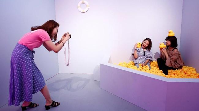 Instalasi yang paling populer adalah 'kolam bola' berwarna pastel. Pengunjung sampai mengantre untuk masuk ke dalamnya dan berfoto dengan bola-bola berbentuk hati itu. (REUTERS/Kim Kyung-Hoon)