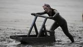Peserta lomba kereta luncur di atas lumpur dalam ajangOlympiade Lumpur. REUTERS/Morris Mac Matzen