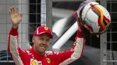Pebalap Ferrari Sebastian Vettel menyapa penggemar di Sirkuit Hockenheim setelah merebut pole di babak kualifikasi GP Jerman. (REUTERS/Wolfgang Rattay)