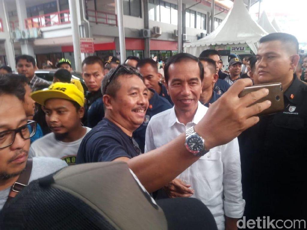 Banyak orang menyiagakan kamera ponselnya di dekat Jokowi sambil tersenyum