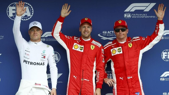 Sebastian Vettel pose bersama Valtteri Bottas (kiri) dan Kimi Raikkonen usai babak kualifikasi GP Jerman. (REUTERS/Ralph Orlowski)