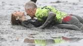 Dua peserta terjatuhdi antara lumpur dalam ajangOlimpiade Lumpur di(AFP PHOTO / Patrik STOLLARZ)