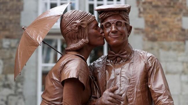 Ada pula yang melumuri diri mereka dengan cokelat, sehingga seperti patung cokelat. (REUTERS/Yves Herman)