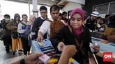 Penumpang menunjukkan tiket kertas yang sudah dibeli sebelum memasuki peron kereta di Stasiun Bekasi, Jawa Barat, Senin, 23 Juli 2018. (CNNIndonesia/Safir Makki)