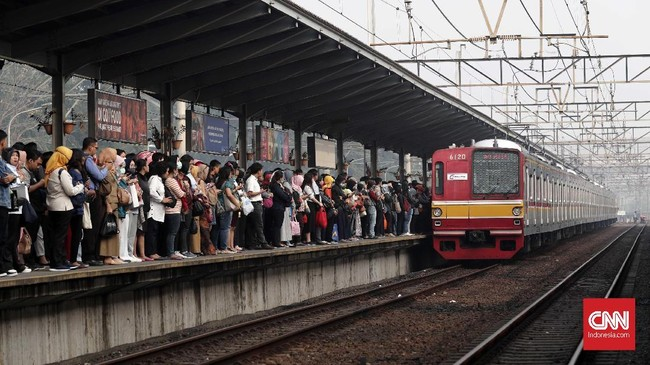 Calon penumpang antre menunggu kereta di Stasiun Bekasi, Jawa Barat, Senin, 23 Juli 2018.Akibat pembelian tiket kertas yang mengular, di sejumlah stasiun keberangkatan beredar para calo yang menjual tiket kertas sementara tersebut. (CNNIndonesia/Safir Makki)